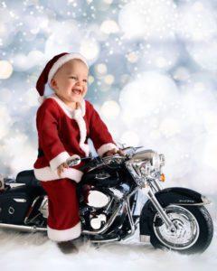 Bebê vestido de papai noel em moto